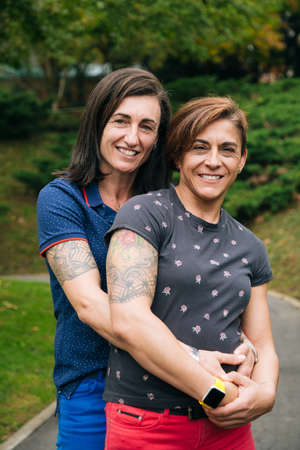 Portrait of a happy middle aged lesbian couple hugging and looking to camera in a park