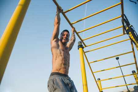 Athletic young man hanging from the bars at the calisthenics gym outdoors smiling