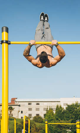Young athletic man doing gymnastics on bars at a calisthenics gym outdoors Standard-Bild