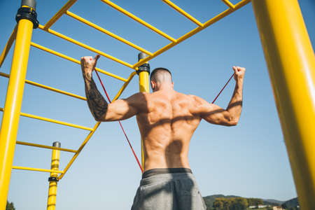 Athletic young man warm up by stretching a resistance band before exercises at the calisthenics gym outdoors