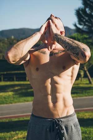 Athletic young man warm up by stretching neck before exercises at the calisthenics gym outdoors