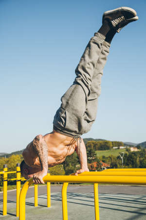 Young urban athlete doing a diagonal handstand on parallel bars at a calisthenics gym outdoors Standard-Bild
