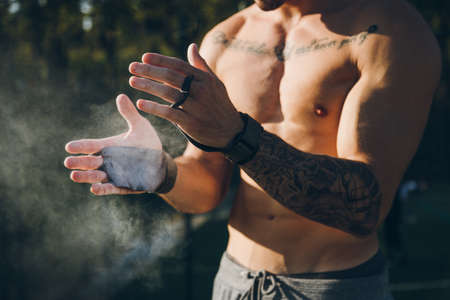 Young urban athlete with  protective gym grips clapping hands with magnesium chalk for calisthenics outdoor. Focus on the hands Standard-Bild