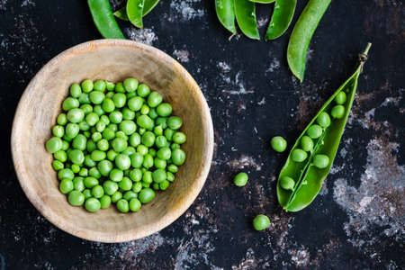 Wooden bowl and pods of raw green peas on a dark rough background Standard-Bild