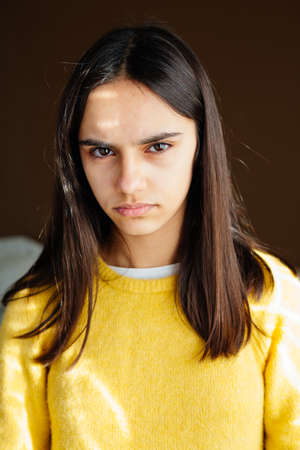 Portrait of an unhappy and displeased teen girl with a yellow sweater at home looking at camera