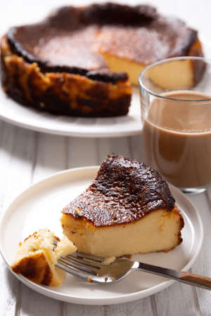 Traditional basque burnt cheesecake with a cup of coffee on a white wooden table. Standard-Bild