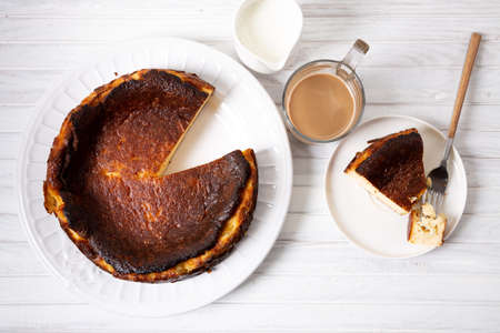 Traditional basque burnt cheesecake with a cup of coffee on a white wooden table. Top view