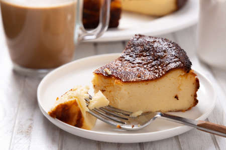 Portion of the traditional basque cheesecake with a cup of coffee