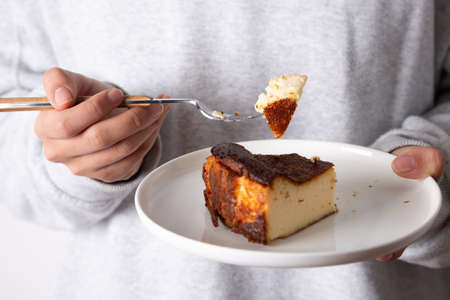 Unrecognizable woman eating a slice of a traditional basque burnt cheesecake