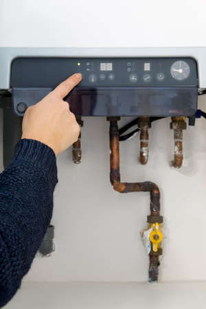 Woman hand switching on the heating boiler at home