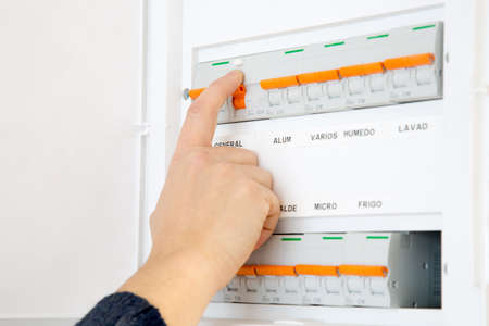 Woman hand switching off the fuse box at home. Words in spanish Standard-Bild