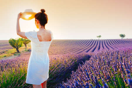 Young woman with hair bun and white dress covering the sun with her hat in a lavender field in Valensole, France, at sunset
