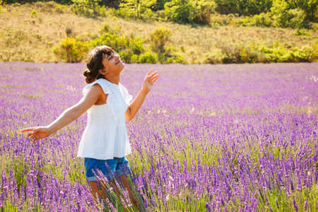 Girl with a hair bun, white blouse and denim shorts enjoying nature and summer in a french lavender field