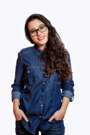 Portrait of a young confident woman with long wavy hair and glasses in denim shirt smiling with hands in the jean pockets. Isolated on white Standard-Bild