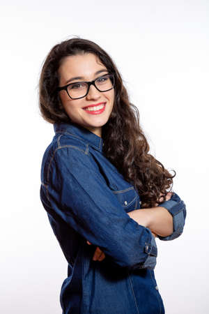 Portrait of a young confident woman with long wavy hair and glasses in denim shirt smiling with arms crossed. Isolated on white
