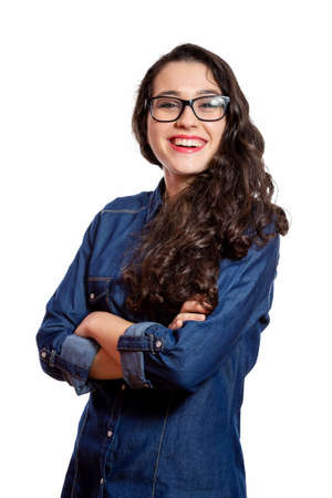 Portrait of a young confident woman with long wavy hair and glasses in denim shirt laughing with arms crossed. Isolated on white