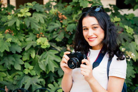 Young beautiful woman taking pictures with a retro camera in a city park Standard-Bild