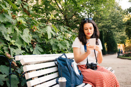 Beautiful tourist woman using her smartphone sitting in a city park bech