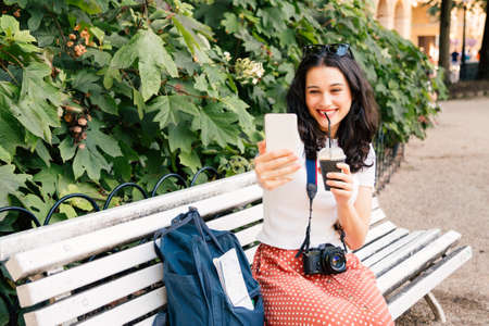 Young beautiful tourist woman with an ice coffee taking a selfie for her followers Standard-Bild