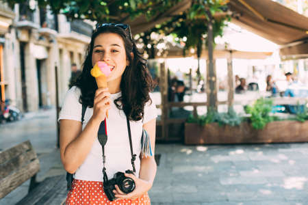 Happy young beautiful tourist woman enjoying a big ice cream in the street.