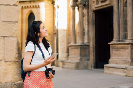 Young tourist woman using the travel guide in her smart phone in front of an ancient church