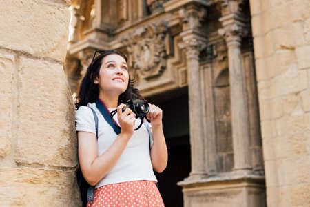 Young tourist woman taking pictures of ancient monuments with a retro camera Standard-Bild