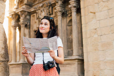 Young tourist woman visiting the old town in an european city with a map