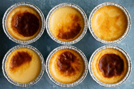 Freshly homemade flan or creme caramel in their molds on a blue rough background. Top view