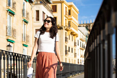 Young happy tourist woman with sunglasses visiting the Old Town in Donostia, Spain, in summer Banque d'images