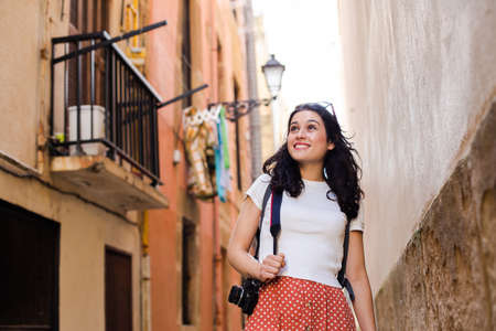 Young happy tourist woman walking down an european city alley with a vintage camera