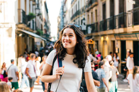 Happy young tourist woman visiting the lively Old Town of San Sebastian, Spain, in summer