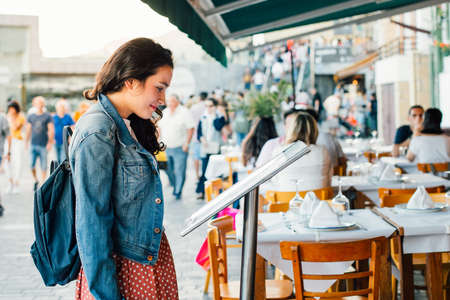 Young tourist woman looking the menu of a restaurant with terrace in the seaport of San Sebastian, Spain, in summer.