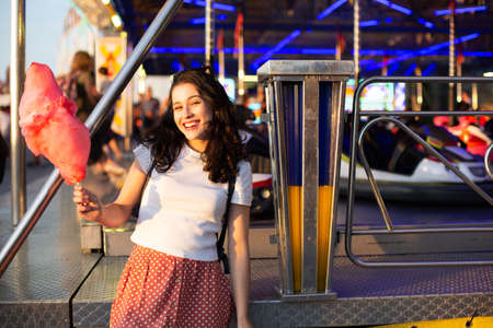 Happy young beautiful woman eating cotton candy at fairground at sunset