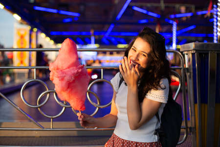 Funny young beautiful woman eating cotton candy at fairground at sunset