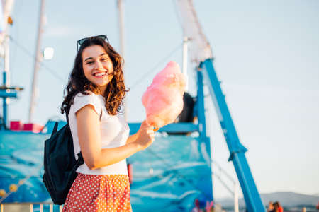 Happy young beautiful woman eating cotton candy at fairground