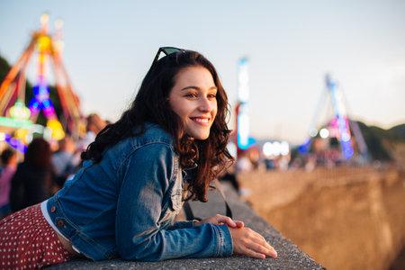 Happy young woman enjoying the sunset at fun fair in San Sebastian, Spain, in summer