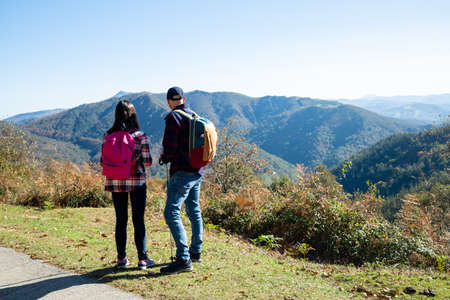 Father and his teenage daughter with backpacks and sticks hiking in autumn looking at the landscape in a sunny day. Back view Banque d'images
