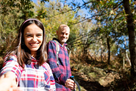 Father and teenage holding hands hiking and looking at camera smiling in the forest. Point Of View Shoot Banque d'images