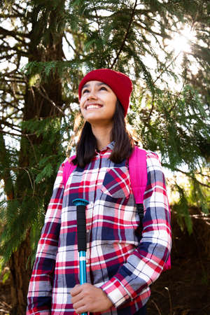 Portrait of a happy teen girl hiker with a plaid shirt and red woolen cap looking up under a pine tree in an autumn sunny day