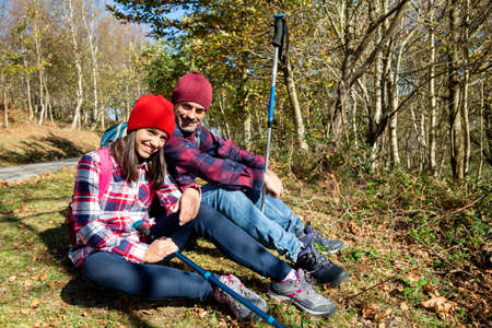 Happy father and teenage daughter sitting on the grass resting after the walk in the mountain in autumn