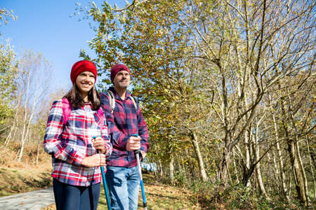 Happy father and his teenage daughter hiking and enjoying the views in a sunny autumn day