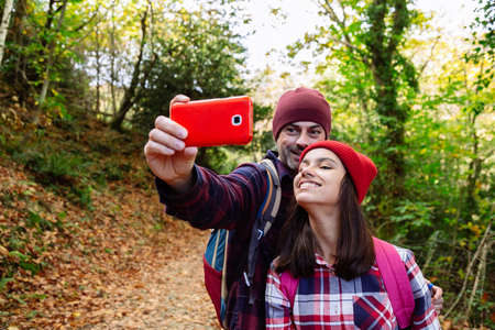 Happy father and teenage daughter taking a selfie during the journey in autumn Banque d'images