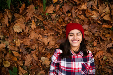 Happy teen girl with a plaid shirt and  red woolen cap lying in a bed of dry leaves with eyes closed  in autumn