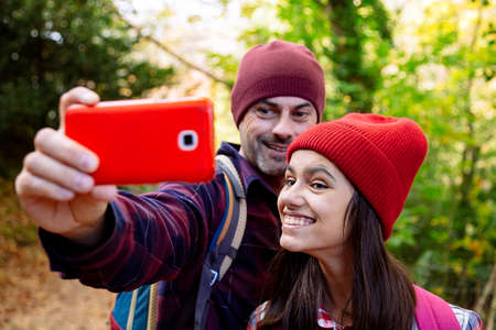Happy father and teenage daughter taking a selfie and making funny faces during the journey in autumn Banque d'images