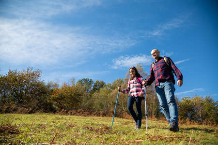 Happy father and teenage daughter hiking in a sunny autumn day