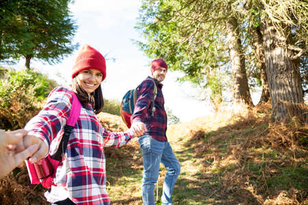 Father and teenage holding hands hiking and looking at camera smiling. Point Of View Shoot Banque d'images