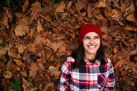 Happy teen girl with a plaid shirt and  red woolen cap lying in a bed of dry leaves and laughing in the forest in autumn