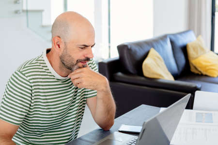 Middle aged man with striped t-shirt working from home with his laptop in the living room Banque d'images