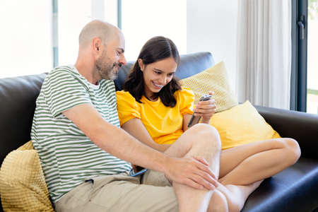 Happy father and teen daughter watching something in her smart phone or having a video call sitting in the sofa
