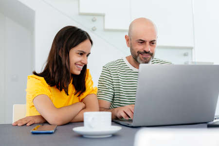 Smiling teen girl with braces looking at her father working from home in the laptop. Focus on her